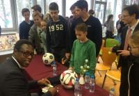 Pablo Thiam signiert Bälle und Karten für die Schüler